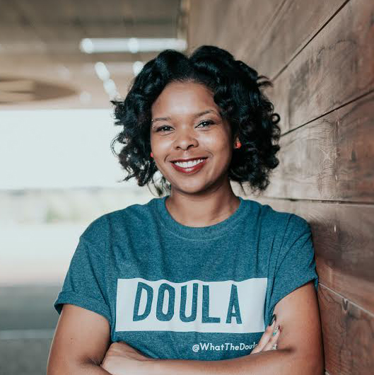 doula kaila matthews wears a teal shirt with the word doula on it, arms crossed, smiling